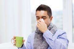 Больной человек с чаем гриппа выпивая и дуя носом Стоковое Фото