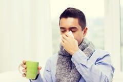 Больной человек с чаем гриппа выпивая и дуя носом Стоковое Изображение