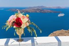 Большая ваза с цветками против моря Стоковая Фотография