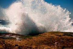 Большая волна ломая на утесах Стоковая Фотография