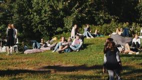 Большая группа в составе молодые люди имеет потеху и ослабляет снаружи на солнечное но также ветреный день сток-видео