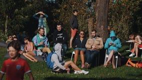 Большая группа в составе молодые люди охлаждая вне снаружи на солнечное но также ветреный день акции видеоматериалы