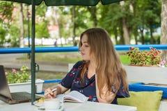 Большая девушка размера работая в кафе стоковое фото rf