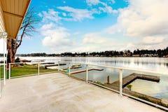 Большая задняя палуба обозревая чудесное озеро и деревянный док Стоковое Изображение RF
