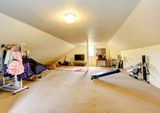 Большая длинная игровая комната чердака с ТВ, шкафом одежды и оборудованием спорта Стоковые Изображения RF