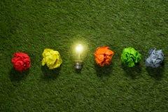 Большая концепция при скомканная бумага и электрическая лампочка офиса стоя на таблице Стоковые Изображения