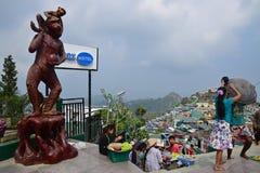 Большая коричневая статуя обезьяны на левой стороне с общиной снабжения жилищем на праве за золотым утесом (пагода Kyaiktiyo) Стоковое фото RF