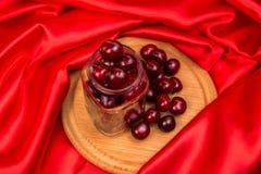 Большая красная вишня в опарнике Стоковые Изображения