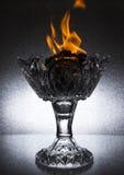 Большая кристаллическая ваза с огнем на верхней части стоит на стеклянном столе стоковое фото rf