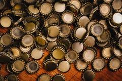Большая куча крышек пивной бутылки на деревянном столе Стоковые Изображения