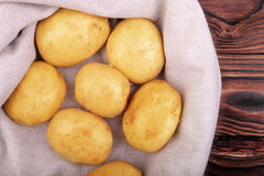 Большая куча русых молодых картошек на серой сумке и на деревянной предпосылке Сбор лета Стоковые Фото