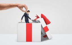 Большая мужская рука получая крошечного бизнесмена вне от белой подарочной коробки с красным смычком на белой предпосылке Стоковое Фото