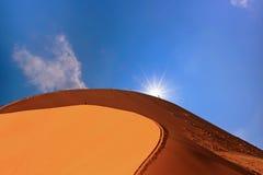 Большая песчанная дюна в Намибии при солнце смотря прищурясь над краем Стоковое Изображение RF