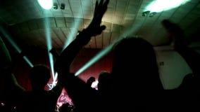 Большая толпа вентиляторов поднимает их оружия на концерте, живой музыке, вентиляторах веселя хлопающ аплодировать сток-видео