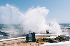 Большие волны ломая на обваловке и причине повреждают Стоковые Фото