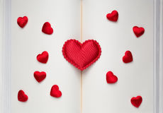Большие и малые красные сердца на открытой книге Стоковое Изображение