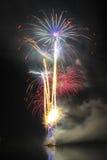 Большие красочные фейерверки над ночой вода Стоковые Фото