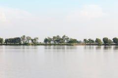 Большие открытые пруд и дерево выстраивают в ряд с горой предпосылки Стоковые Изображения