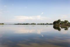 Большие открытые пруд и дерево выстраивают в ряд с горой предпосылки Стоковое Фото