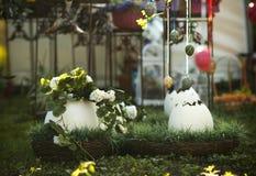 Большие пасхальные яйца украсили цветки в коричневые плетеные корзины стоковое фото rf