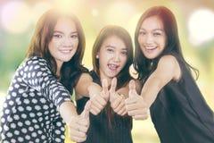 Большие пальцы руки выставки девочка-подростков вверх с предпосылкой bokeh Стоковое Фото