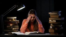 Большие пальцы руки девушки через книгу и ее ушибают головные боли Черная предпосылка видеоматериал