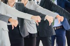Большие пальцы руки команды бизнесмена и женщины ginving вниз стоковое изображение