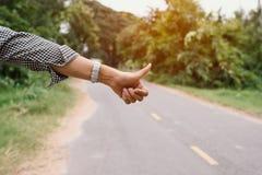 Большие пальцы руки на предпосылке дороги Стоковое Фото
