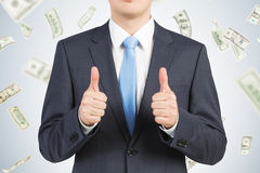 Большие пальцы руки поднимают бизнесмена в дожде доллара Стоковые Фото