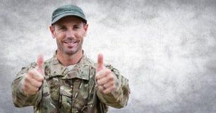 Большие пальцы руки солдата вверх против белой стены с верхним слоем grunge Стоковая Фотография