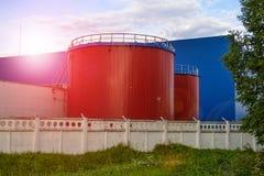Большие промышленные танки красного цвета против голубого промышленного здания Стоковые Фотографии RF