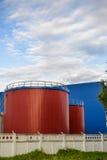Большие промышленные танки красного цвета против голубого промышленного здания Стоковые Изображения RF