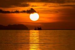 Большие солнце и силуэт рыбацкой лодки Стоковое Изображение