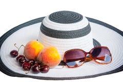 Большие шляпа, плодоовощи и стекла пляжа от изолированного солнца Стоковое Фото