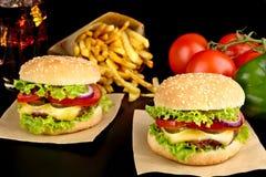 Большие cheeseburgers на бумаге, фраях француза и стекле колы на черноте Стоковые Изображения