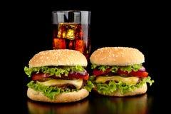 Большие 2 cheeseburgers с стеклом колы на черном деревянном столе Стоковая Фотография RF