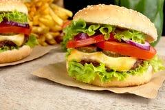 Большие cheeseburgers с французскими фраями на деревянном столе Стоковая Фотография