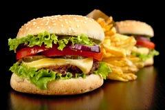 Большие cheeseburgers с французскими фраями на черной доске Стоковое фото RF