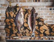 2 больших копченых рыбы висят на предпосылке штабелированного швырка Стоковые Фото