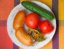 2 больших сосиски и овоща на белом блюде. Стоковые Фото