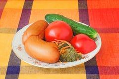2 больших сосиски и овоща на белом блюде. Стоковое Фото