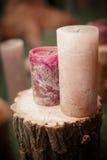 2 больших фиолетовых свечи на деревянном пне Стоковые Фото