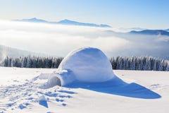 Большое круглое иглу стоит на горах покрытых с снегом Стоковое Изображение