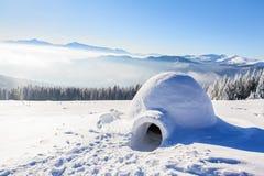 Большое круглое иглу стоит на горах покрытых с снегом Стоковые Фото