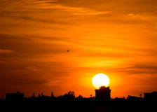Большое солнце на линии города силуэте захода солнца оранжевой стоковое изображение rf