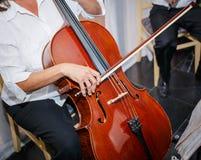 Большой взгляд крупного плана персоны сидя и практикуя на аппаратуре виолончели музыкальной старой винтажной Стоковые Изображения RF