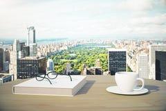 Большой вид на город с чашкой кофе, книгой и стеклами стоковые изображения