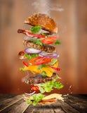 Большой вкусный бургер с ингридиентами летания Стоковые Изображения