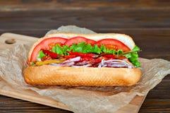 Большой вкусный хот-дог с соусом и овощами в пергаменте на деревянной предпосылке гурман горячей сосиски Стоковая Фотография RF