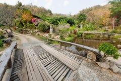 Большой деревянный мост над рекой в старой тайской деревне с деревьями вокруг Стоковое Изображение
